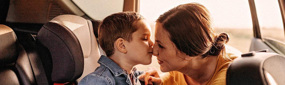 Mulher colocando cinto de segurança em uma criança