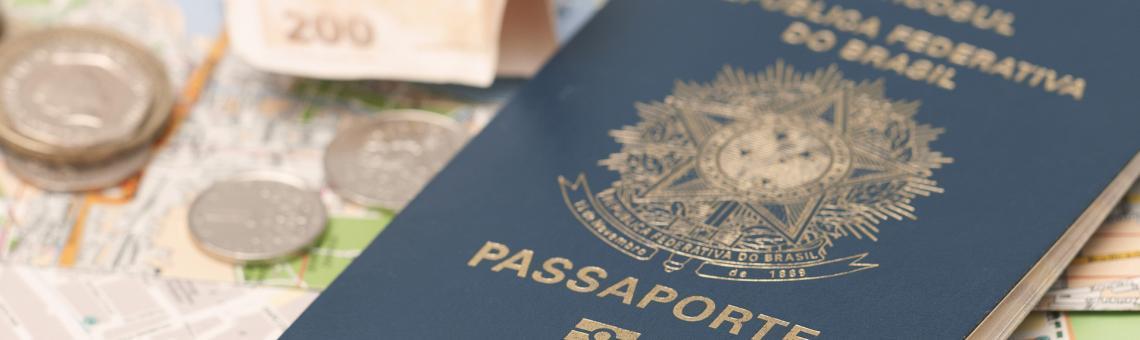 Imagem de um mapa de ruas de uma cidade, e em cima dele um passaporte do Brasil e algumas moedas e notas de dinheiro.