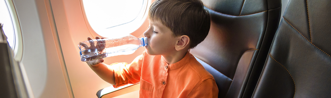 Image of a boy drinking water from a bottle on the plane.