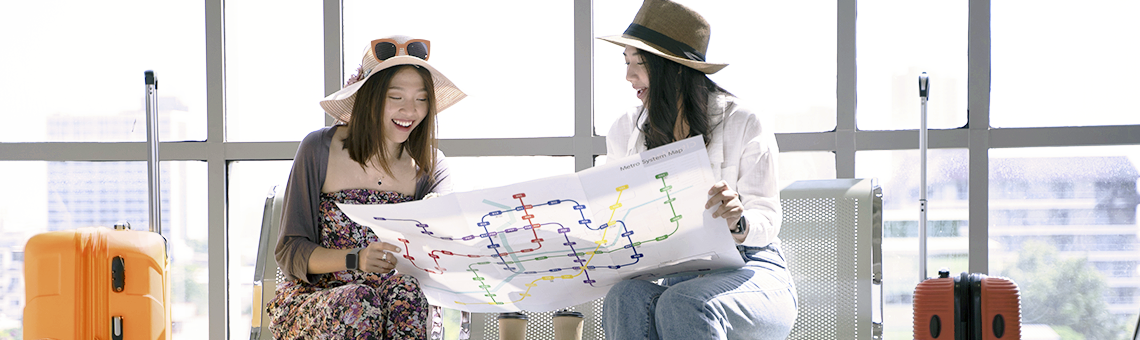 Two happy oriental young women sitting at the airport holding and looking at a large open map
