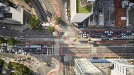 Imagem aérea de um cruzamento em uma avenida, cheia de carros e pessoas.