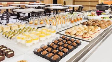 Imagem de um buffet com doces, salgados, bebidas, etc.