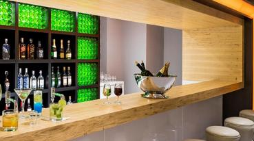 Imagem de um bar com varias bebidas em uma estante, varias bebidas em cima do balcão da frente e alguns banquinhos na frente do bar.