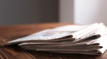 Imagem de alguns jornais em cima de uma mesa.