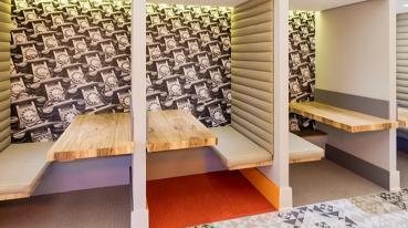 Imagem mostrando uma sala de espera com duas mesas, com assentos.