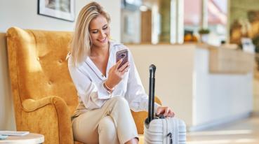 Mulher loira sentada em uma poltrona laranja, segurando sua mala branca e olhando feliz para tela de seu celular conectado no wifi das salas premium lounge.