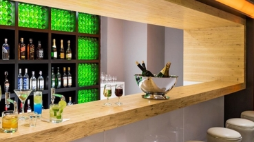 Image showing a bar with various drinks behind a counter and some stools in front of the bar