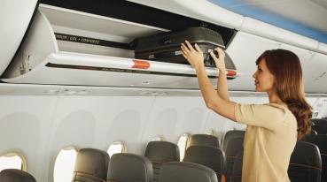 Imagen de una mujer poniendo su equipaje en el portaequipajes encima del asiento.
