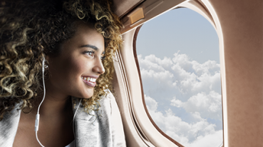 Young mixed race woman smiles while looking through window on aircraft. She is wearing earbuds.