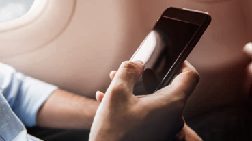 Passenger holding cell phone in hand inside the plane In-Seat Power